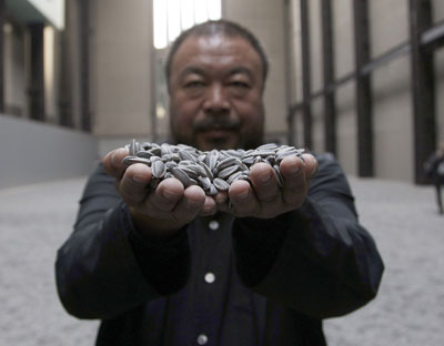 Ai Weiwei, con un puñado de sus pipas de porcelana, ayer, en Londres.