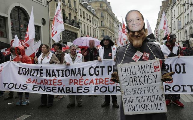 Un manifestante posa con una careta de Hollade y una máscara de Sarkozy.